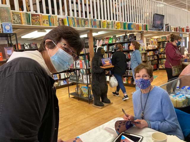 janice detrie signing her book for a customer in bookstore