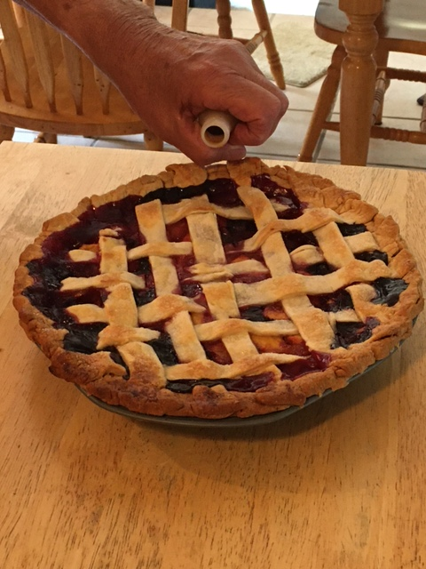 finished pie with a hand next to the pie